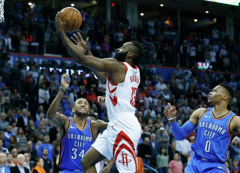 Houston Rockets guard James Harden, center, shoots between Oklahoma City Thunder guard Josh Huestis (34) and guard Russell Westbrook (0) in the first half of an NBA basketball game in Oklahoma City, Tuesday, March 6, 2018. (AP Photo/Sue Ogrocki) Photo: Sue Ogrocki, Associated Press / AP2018