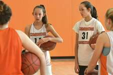 Cambridge twin sisters Lilly, left, and Sophie Phillips listen to their coach during basketball practice on Tuesday, March 6, 2018 in Cambridge, N.Y. The freshman pair are the team's leading scorers. (Lori Van Buren/Times Union)