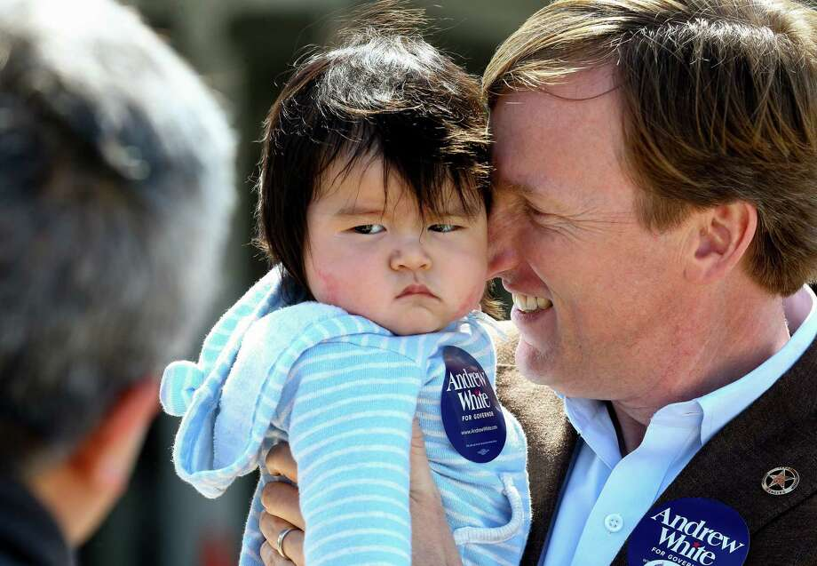 Gubernatorial candidate Andrew White, right, holds six-month-old Max while talking to Max's father Peter Kim, foreground, outside the West Gray Recreation Center  Tuesday, March 6, 2018, in Houston. ( Godofredo A. Vasquez / Houston Chronicle ) Photo: Godofredo A. Vasquez / Houston Chronicle
