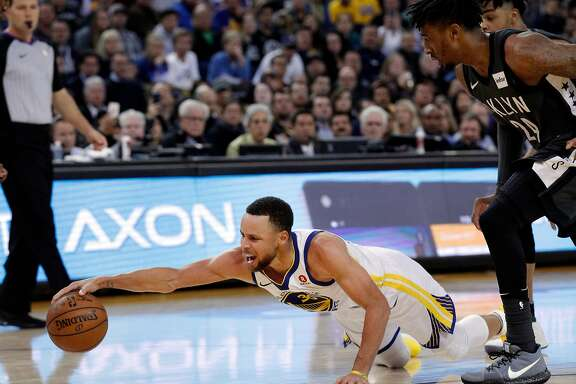 Stephen Curry (30) goes tumbling to the court after being tripped in the second half as the Golden State Warriors played the Brooklyn Nets at Oracle Arena in Oakland, Calif., on Tuesday, March 6, 2018.