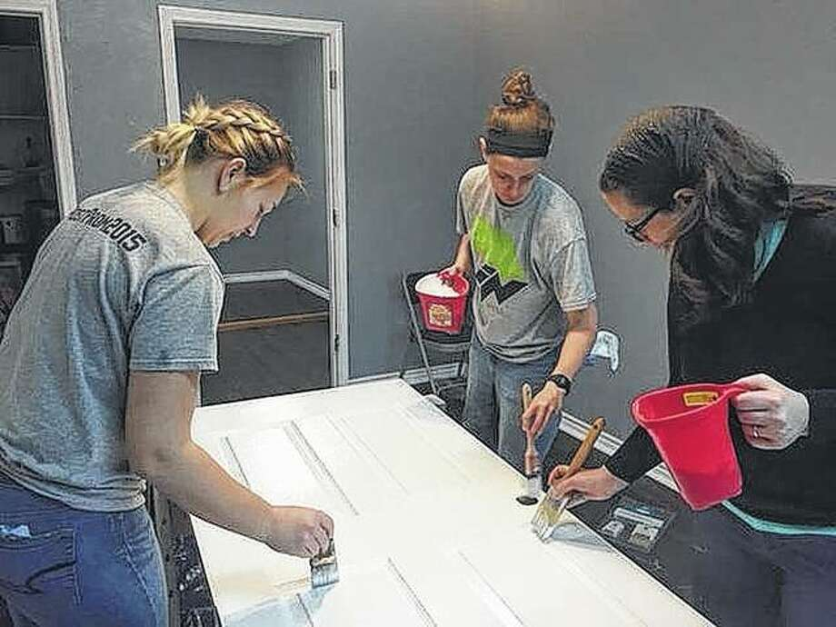 Olivia Jordan, Charolette Crofton and Illinois College professor Abby Musgrove paint a door as part of repair work being done during the college's spring break. Photo: Photo Provided