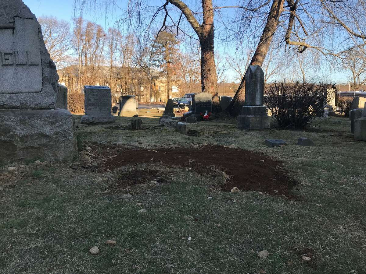 A mound of fresh dirt in the foreground is where police found human bone fragments earlier this week in a near-forgotten cemetery in Springdale.