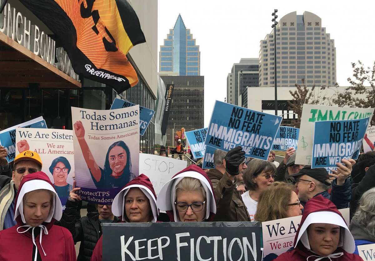 Sacramento's Handmaids Coalition stand on the front lines as protesters gather outside of the Sawyer Hotel Wednesday, March 7, 2018 in Sacramento, Calif. ahead of U.S. Attorney General Jeff Session's expected announcement regarding sanctuary jurisdiction.