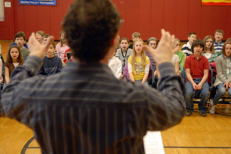 Albany Symphony Orchestra conductor David Alan Miller, foreground, rehearses with George Washington School, and Poestenkill Elementary school students at George Washington School in Brunswick, NY on Monday, March 16, 2009, in preparation for the world premiere performance of an orchestral piece by Dorothy Chang that features the children at EMPAC on Friday.   (Paul Buckowski / Times Union) Photo: PAUL BUCKOWSKI, ALBANY TIMES UNION / 00002849A