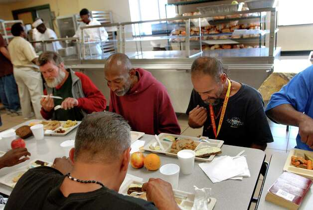 "Samuel ""Poppy"" Baez, right, prays and gives the sign of the cross before having lunch on Tuesday, Sept. 8, 2009, at the Capital Region Rescue Mission in Albany, N.Y. (Cindy Schultz / Times Union) Photo: CINDY SCHULTZ"