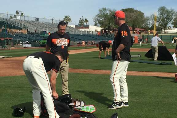 Giants catcher Buster Posey confers with head athletic trainer Dave Groeschner and manager Bruce Bochy after catching drills Wednesday. Posey then took batting practice.