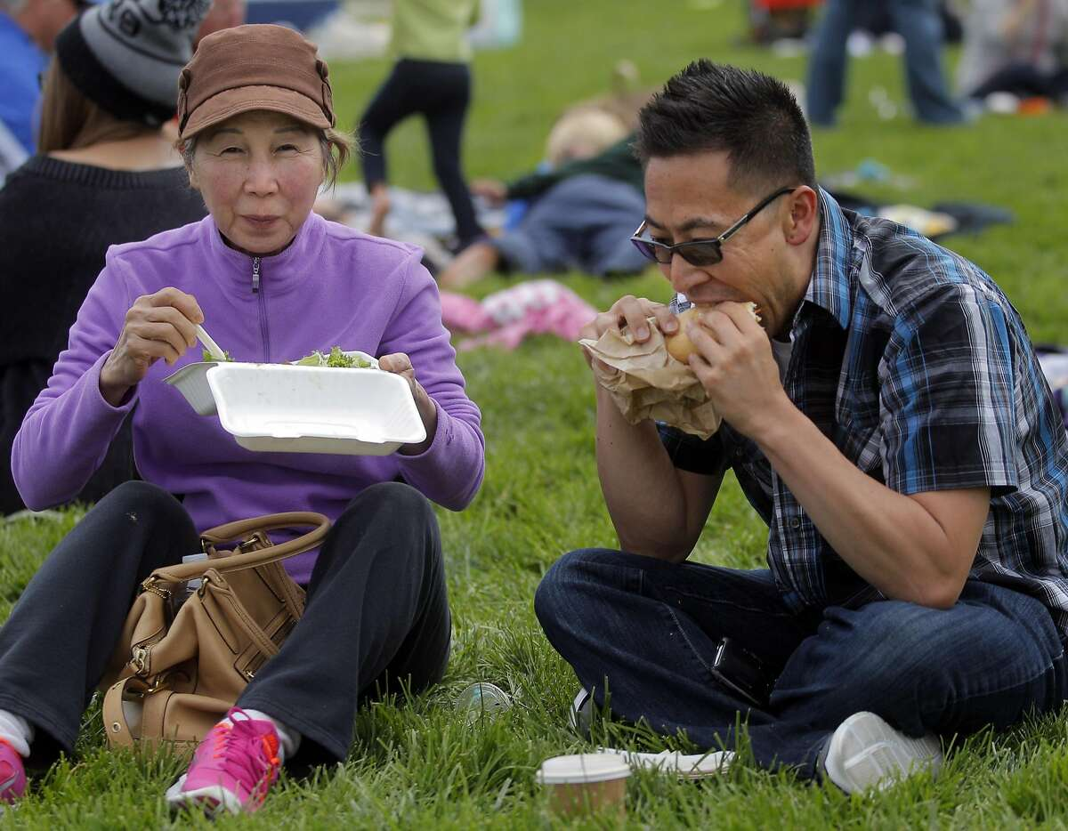 Byron Lam and his mom, Anh Ly, left, enjoy some Vietnamese food at Off the Grid's Sunday Picnic in the Presidio Main Post lawn in San Francisco on Sunday, August 3, 2014.