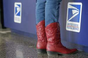 The boots of a customer are shown at the post office booth Wednesday, March 7, 2018 located in Reliant Center during the Houston Livestock Show and Rodeo.