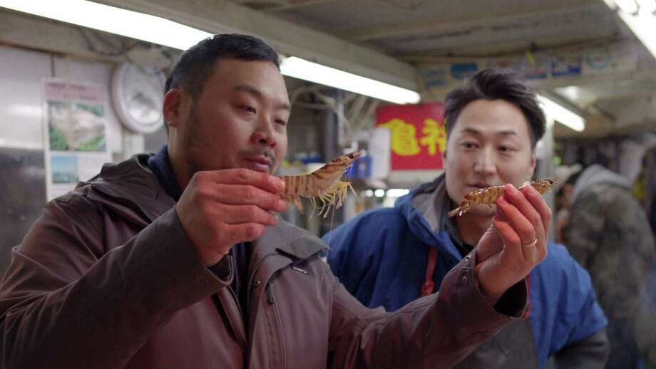 "David Chang (left) scrutinizes shrimp at a fish market during an episode of the new Netflix series ""Ugly Delicious."" Photo: Courtesy Netflix"