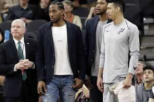FILE - In this Jan. 21, 2018, file photo, San Antonio Spurs guard Danny Green, right, stands at the bench with injured teammates Kawhi Leonard, second from left, and Rudy Gay, center, during the second half of an NBA basketball game against the Indiana Pacers in San Antonio. Leonard plans on returning this season and wants to remain with the Spurs for life, refuting reports of dissension with the star forward and the only franchise he has played for. Leonard has missed all but nine games this season with right quadriceps tendinopathy, which initially flared up late in the offseason.  (AP Photo/Eric Gay, File)