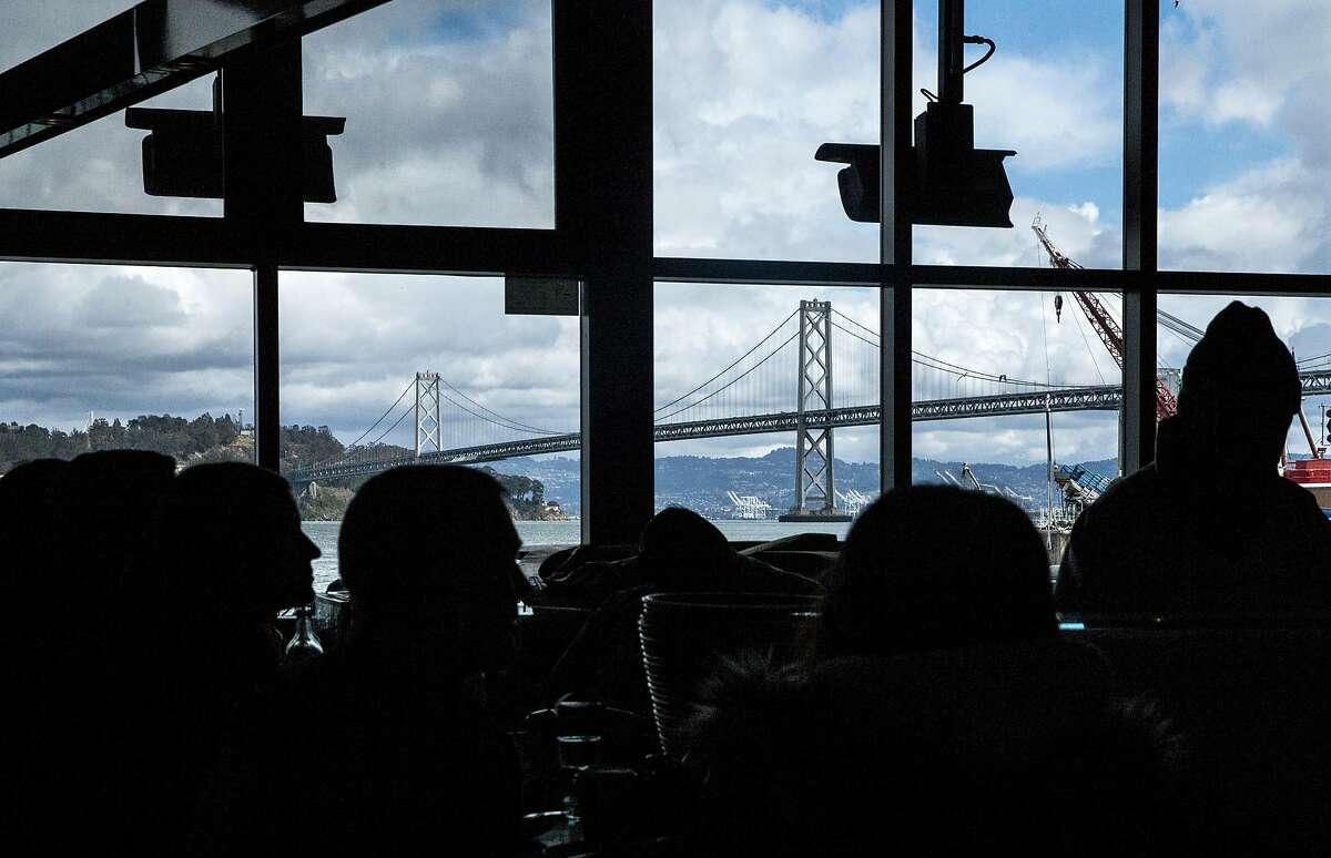 The Bay Bridge is seen through the windows of Hog Island Oyster Company inside the Ferry Building Saturday, March 3, 2018 in San Francisco, Calif.