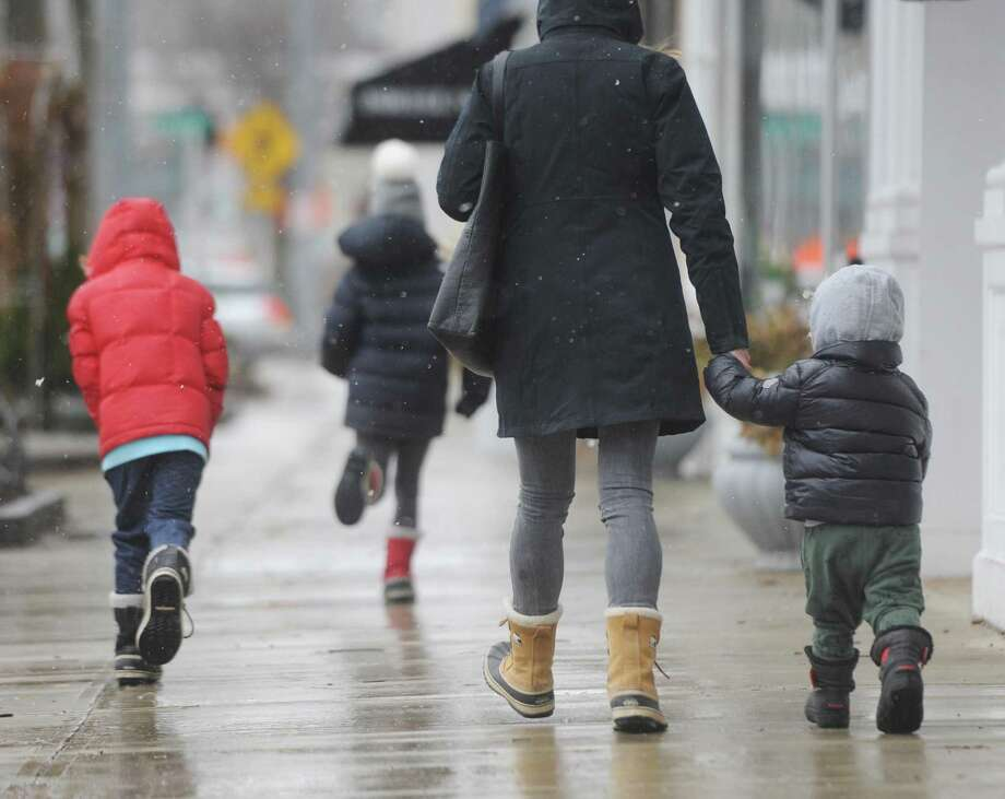 A family walks along a sidewalk as the first flakes of the nor'easter Quinn fall in Old Greenwich, Conn. Wednesday, March 7, 2018. Up to one foot of snow is projected to fall in the area Wednesday. Photo: Tyler Sizemore / Hearst Connecticut Media / Greenwich Time