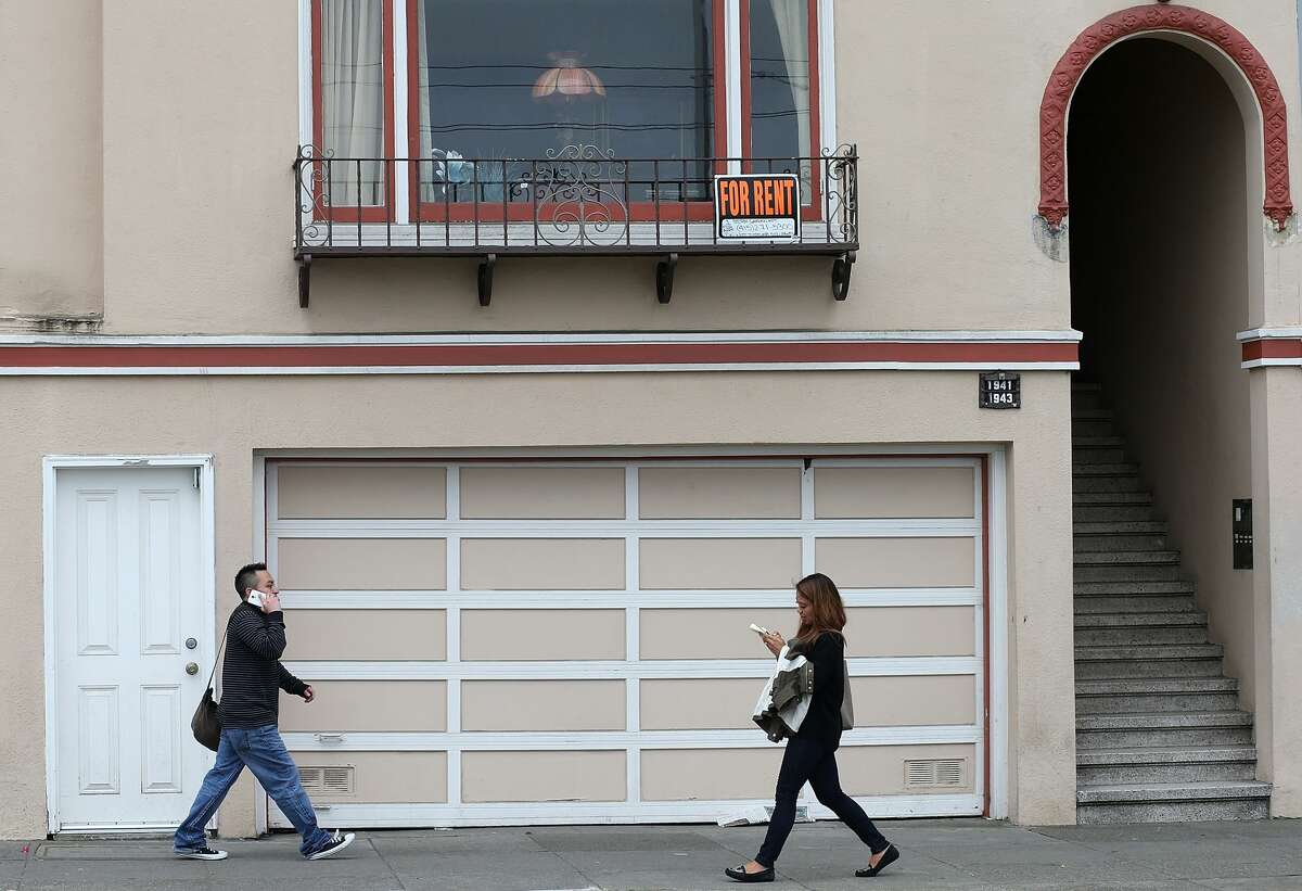 FILE PHOTO: Pedestrians walk by an apartment for rent in San Francisco.