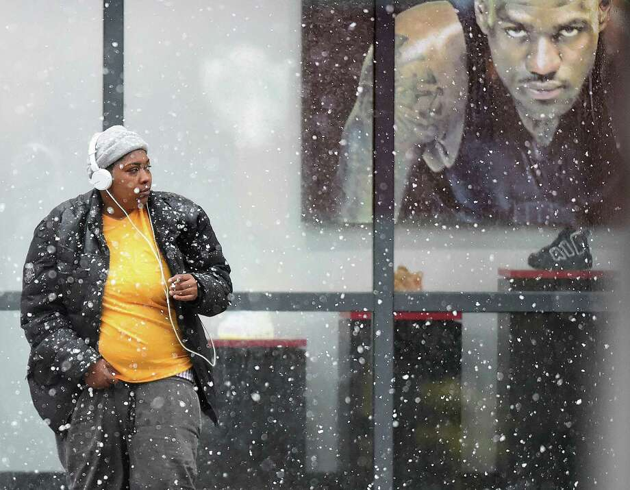 A woman wearing headphones doesn't seem fazed by the weather in downtown New Haven, Wednesday, March 7, 2018, during the nor'easter predicted to bring four to eight inches of snow in the area. Photo: Catherine Avalone / Hearst Connecticut Media / New Haven Register