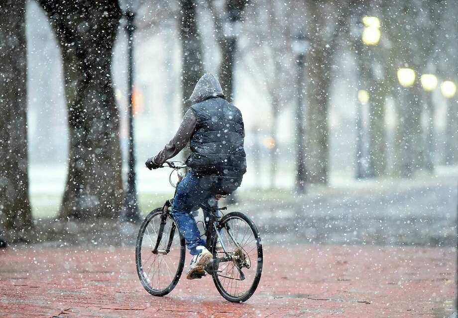 A man riding a bicycle in downtown New Haven, Wednesday, March 7, 2018, during the nor'easter predicted to bring four to eight inches of snow in the New Haven area. Photo: Catherine Avalone / Hearst Connecticut Media / New Haven Register