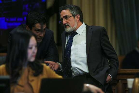 Supervisor Aaron Peskin talks to legislative aide Conor Johnston (center) during a Board of Supervisors meeting at City Hall, in San Francisco, California on Tuesday, February 23, 2016.
