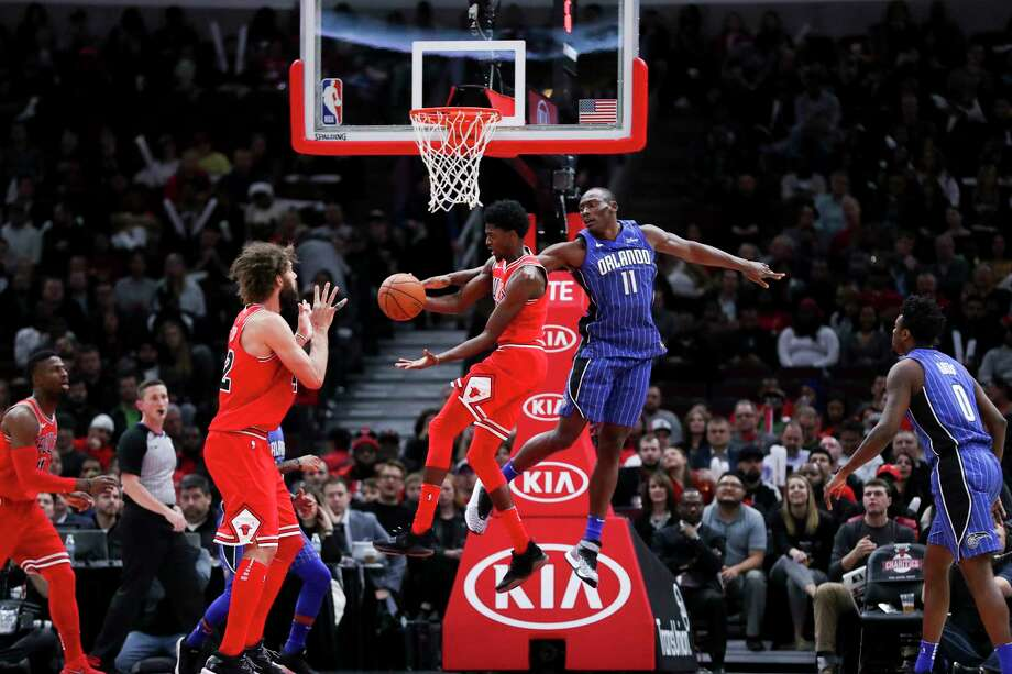 The Orlando Magic's Bismack Biyombo (11) guards the Chicago Bulls' Justin Holiday (7) while he passes the ball to teammate Robin Lopez (42) during the second half at the United Center in Chicago on Wednesday, Dec. 20, 2017. Photo: Armando L. Sanchez, TNS / Chicago Tribune