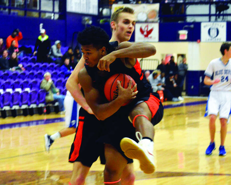 Edwardsville senior R.J. Wilson pulls down a rebound in front of teammate Caleb Strohmeier during a game against Quincy in Collinsville.