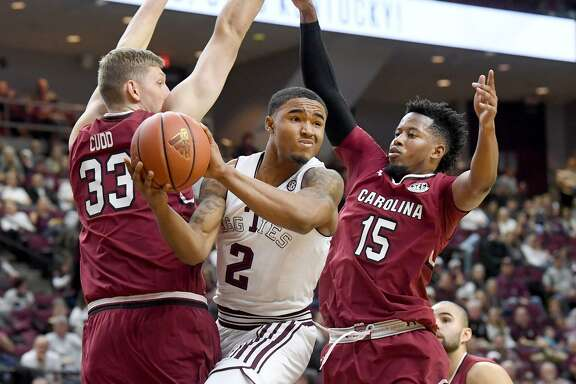 Texas A&M's T.J. Starks (2) passes the ball while between South Carolina's Jason Cudd (33) and Wesley Myers (15) in the first half on Saturday at Reed Arena.