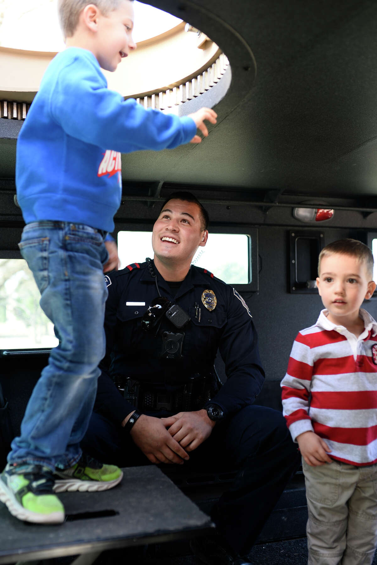 """Midland Police Department officer Joe Mendez talks with young Midlanders inside a Bearcat armored vehicle during a """"Cookies with a Cop"""" event March 7, 2018 at Midland Community Theater. James Durbin/Reporter-Telegram"""