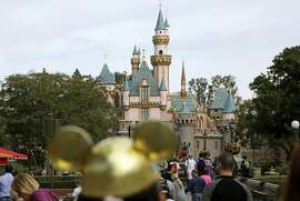FILE - In this Jan. 22, 2015 file photo, visitors walk toward Sleeping Beauty's Castle  at Disneyland Resort in Anaheim, Calif. A power outage Wednesday, Dec. 27, 2017 has hit parts of the Disneyland theme park and stopped some rides. A park representative tells Los Angeles news station KABC-TV that power is out in Toontown and Fantasyland, and guests have been escorted off about a dozen rides. A park statement says the problem involves a transformer at the Disneyland Resort. (AP Photo/Jae C. Hong, File)