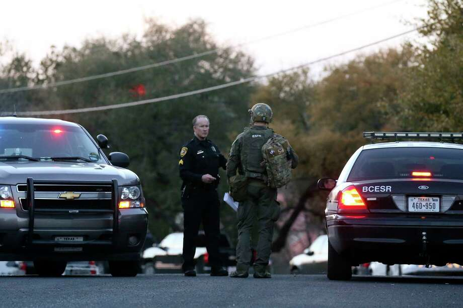 Law enforcement personnel gather near the site of a standoff in the Stage Coach Hills subdivision in northwest Bexar County, Wednesday, March 7, 2018. According to Bexar County Sheriff Department, a man in his 60's barricaded himself with his mother who is in her 80's, Tuesday night. The man fired on deputies and injured two at the house on the 9200 block of Saddle Trail. Photo: JERRY LARA, San Antonio Express-News / © 2018 San Antonio Express-News