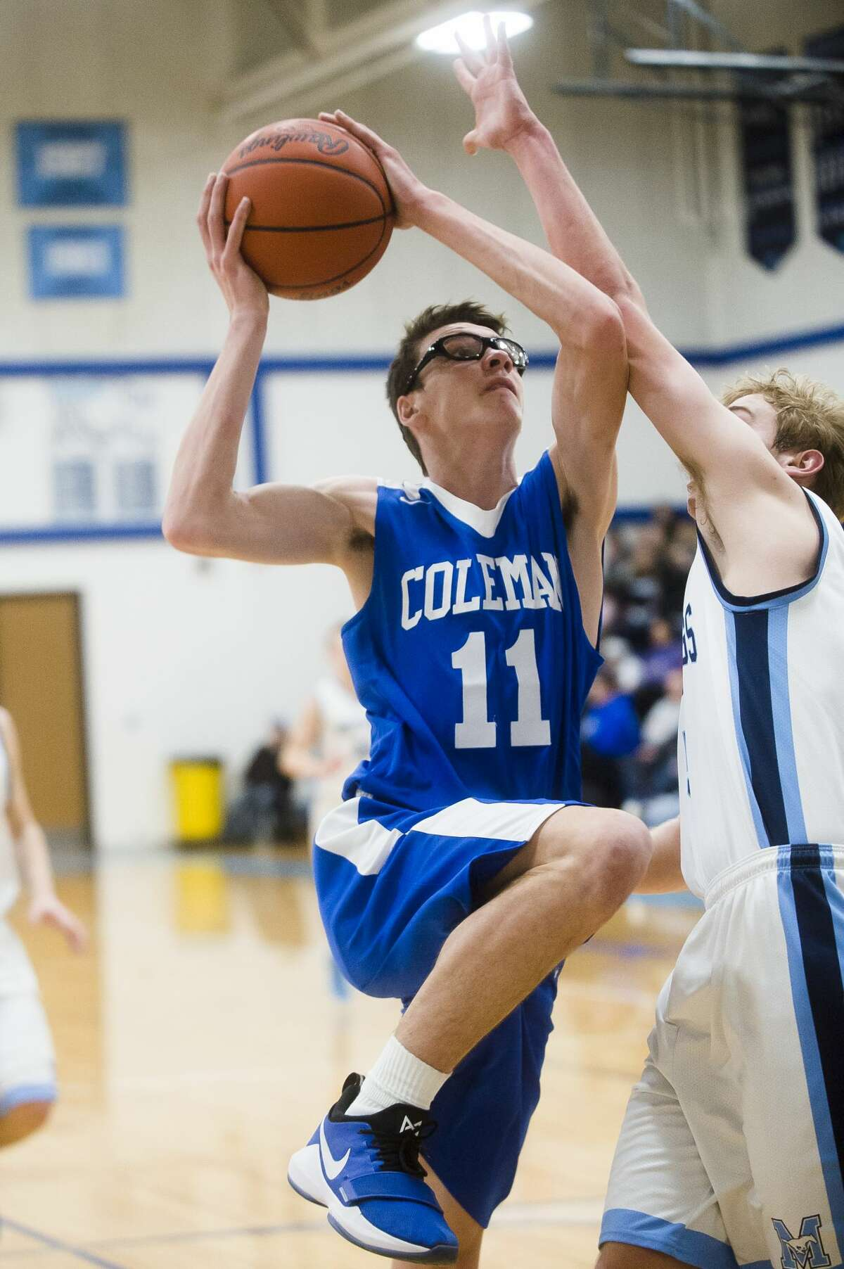 Coleman sophomore Connor Arnold takes a shot while Meridian senior Garrett Stockford guards him during their district semifinals game on Wednesday, March 7, 2018 at Meridian High School. (Katy Kildee/kkildee@mdn.net)