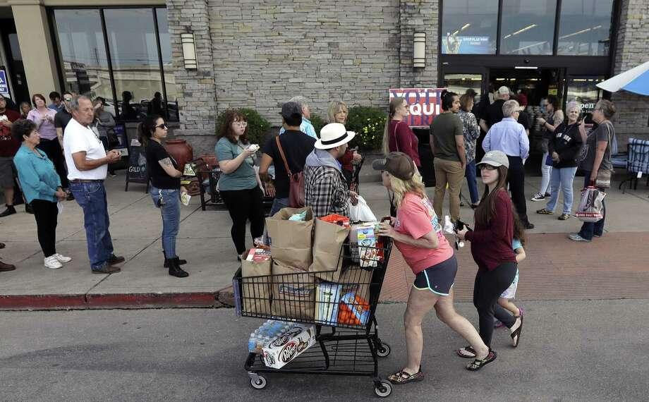 Shoppers in Austin pass a line of voters at a grocery story that also served as a polling site for the Texas primary elections. Photo: Eric Gay / Associated Press / Copyright 2018 The Associated Press. All rights reserved.
