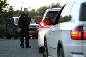Law enforcement personnel check vehicles Wednesday near the site of a standoff in the Stage Coach Hills subdivision in northwest Bexar County.