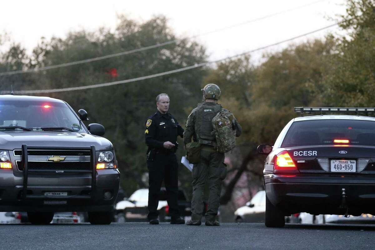 Law enforcement personnel gather near the site of a standoff Wednesday in the Stage Coach Hills subdivision in northwest Bexar County.