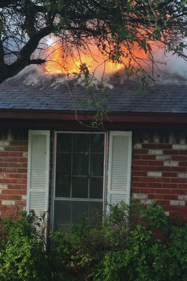 Flames head for the front of the house that heavily damaged a Deer Park home Wednesday afternoon. Photo: Robert Avery