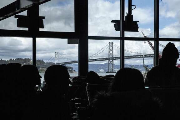 The Bay Bridge is seen through the windows of Hog Island Oyster Company inside the Ferry Building in San Francisco on Saturday, March 3, 2018.