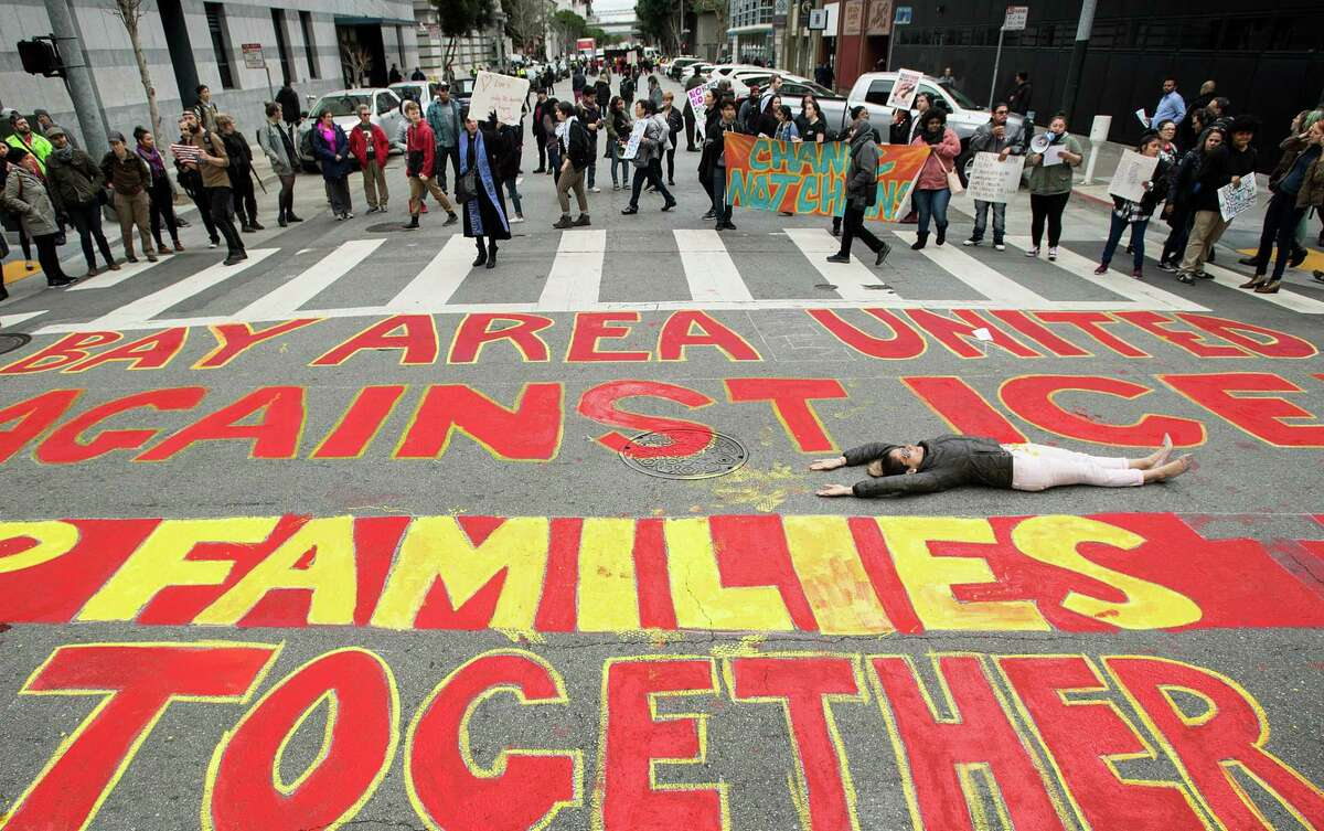 Carolina Collazos lies in an intersection in San Francisco as protesters rally against immigration raids outside the Department of Homeland Security offices on Sansome St. on Wednesday, February 28, 2018.