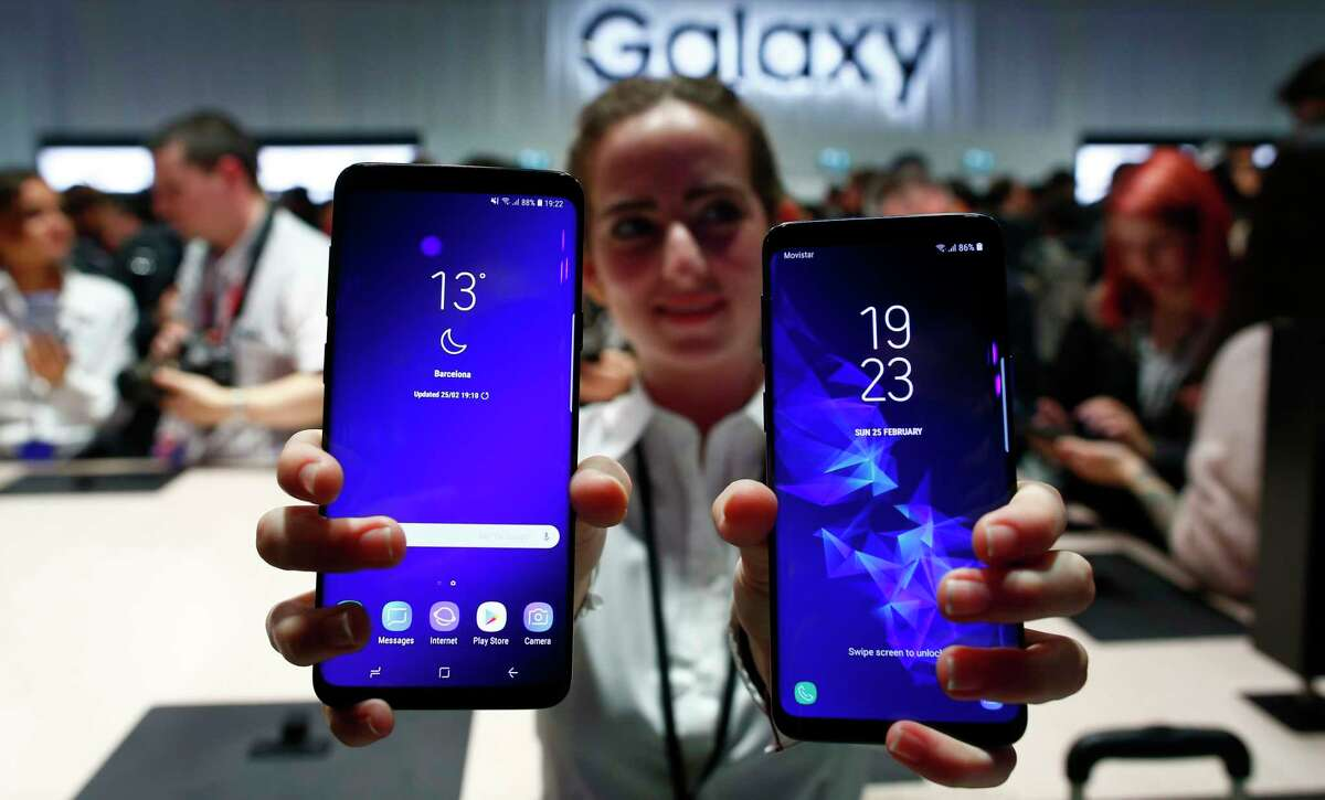 FILE- In this Feb. 25, 2018, file photo, a woman holds the new Galaxy S9 and S9 plus during the Samsung Galaxy Unpacked 2018 event on the eve of the Mobile World Congress wireless show in Barcelona, Spain.