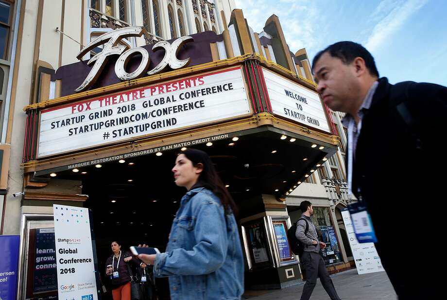 Attendees walk past the Fox Theatre on Broadway in Redwood City during the Startup Grind Global Conference. Photo: Paul Chinn, The Chronicle