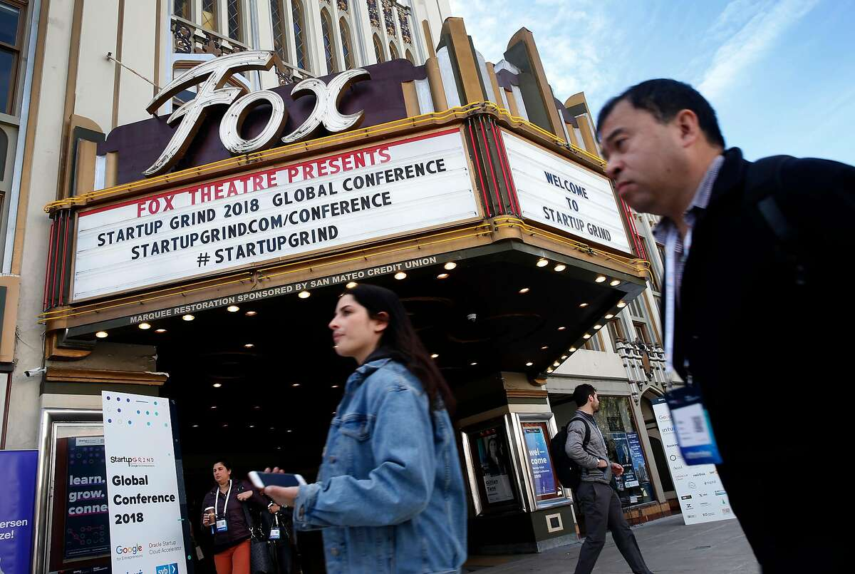 Attendees walk past the Fox Theatre on Broadway in Redwood City, Calif. on the second day of the Startup Grind Global Conference on Wednesday, Feb. 14, 2018.