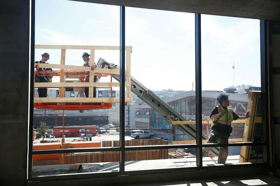 Steve Gomzez (right), a Capitol Glass journeyman, works outside a window at a building under construction in San Francisco where Adobe will have an office in the future. Adobe currently has 1,600 staffers in San Francisco. Photo: Lea Suzuki, The Chronicle