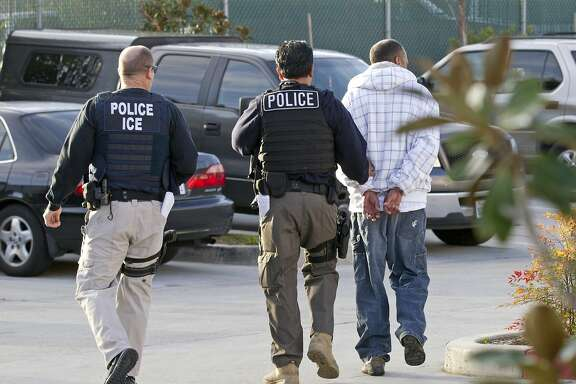 FILE - In this March 30, 2012 file photo, Immigration and Customs Enforcement (ICE) agents take a suspect into custody as part of a nationwide immigration sweep in Chula Vista, Calif. People arrested by deportation officers increasingly have no criminal backgrounds, according to figures released Friday, Feb. 23, 2018, reflecting the Trump administration's commitment to cast a wider net. (AP Photo/Gregory Bull, File)