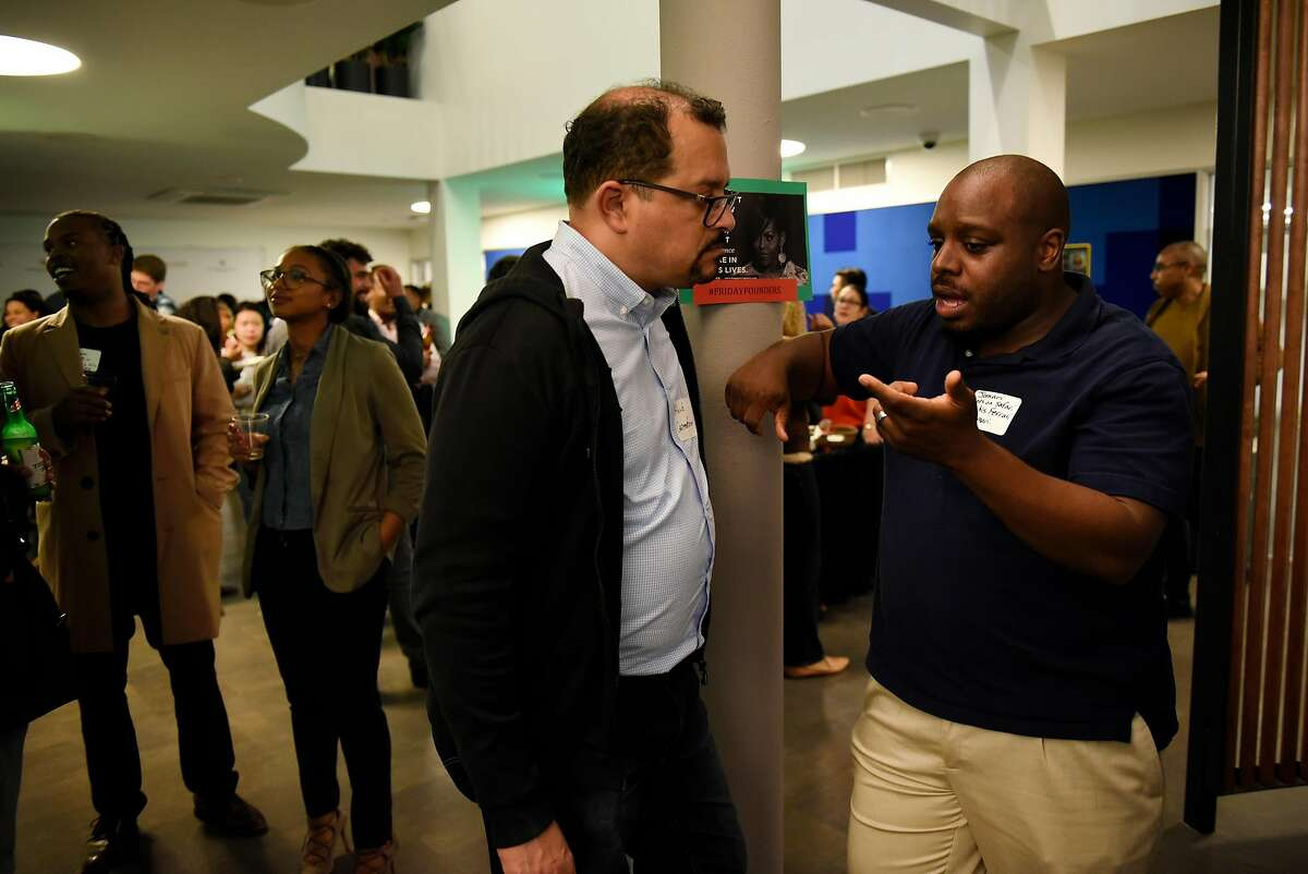 Jomari Peterson, right, and Abiud Amaro Diaz chat during a monthly First Friday mixer for Oakland tech entrepreneurs held at the Kapor Center for Social Impact in Oakland, Calif., on Friday February 2, 2018.