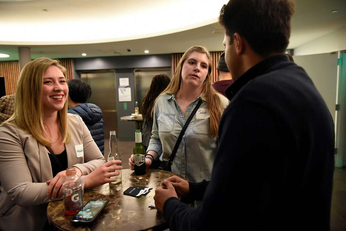 Nicolette Zalesky, left, and Julie Sanders chat with Sumit Singh during a monthly First Friday mixer for Oakland tech entrepreneurs held at the Kapor Center for Social Impact in Oakland, Calif., on Friday February 2, 2018.
