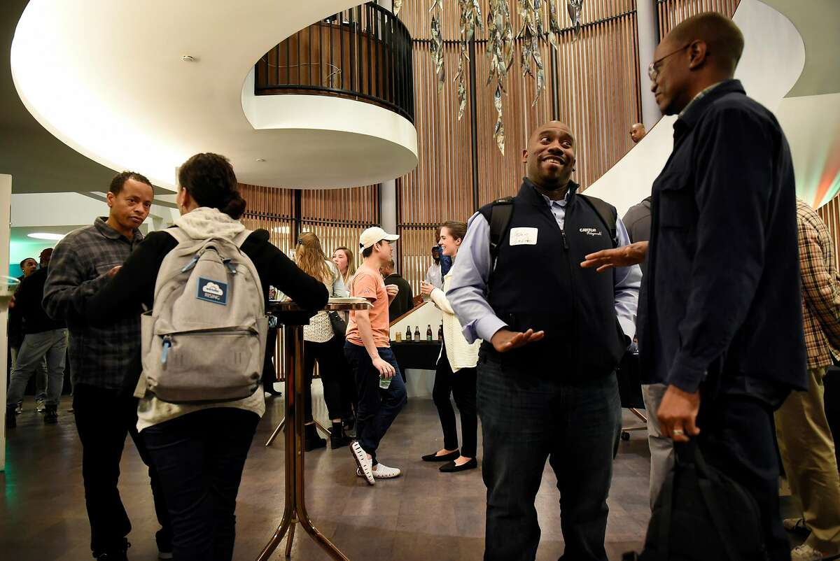 Guests mingle and chat during a monthly First Friday mixer for Oakland tech entrepreneurs held at the Kapor Center for Social Impact in Oakland, Calif., on Friday February 2, 2018.