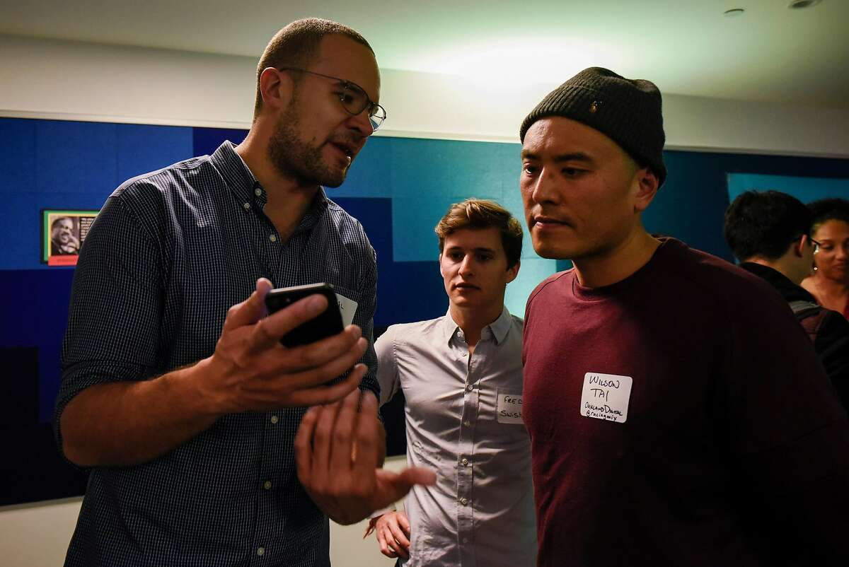 Kahlil Trocome, left, and Fred Bidot, center, show Wilson Tai their Swishh App during a monthly First Friday mixer for Oakland tech entrepreneurs held at the Kapor Center for Social Impact in Oakland, Calif., on Friday February 2, 2018.