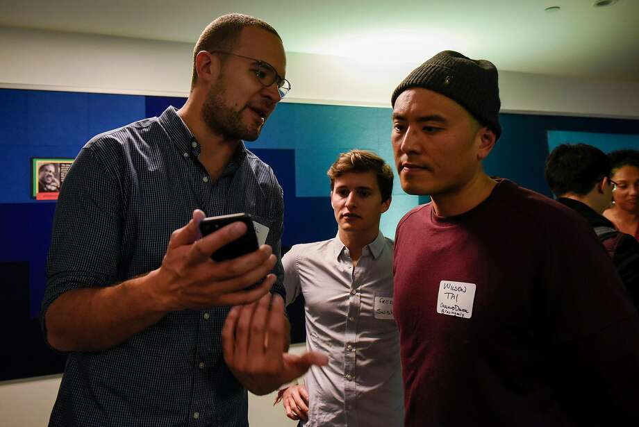 Kahlil Trocome (left) and Fred Bidot show Wilson Tai their Swishh app during a monthly First Friday mixer for the Oakland Startup Network held at the Kapor Center for Social Impact. Photo: Michael Short, Special To The Chronicle