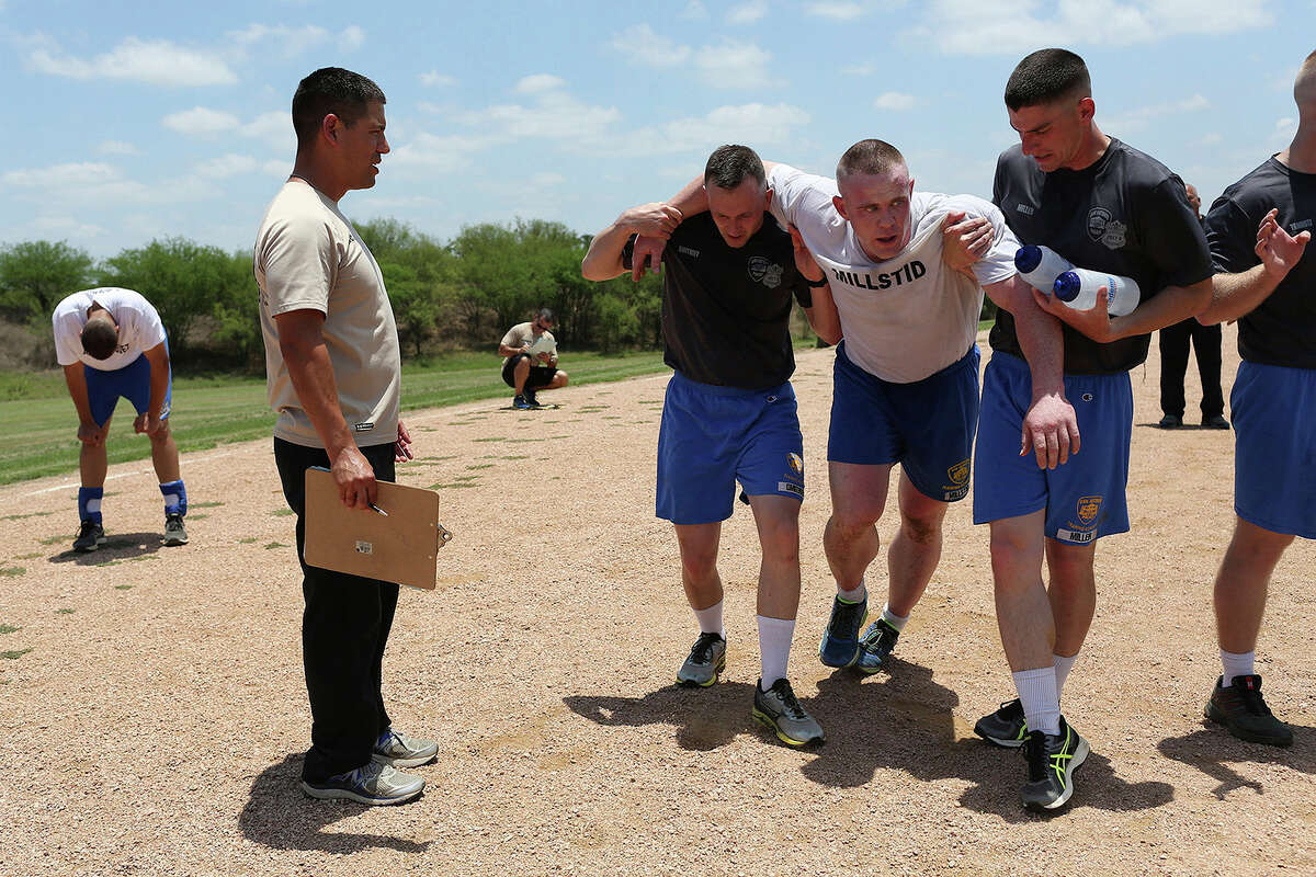 Cadets Philipp Dmitriev, left, and Matthew Miller, right, hold up cadet Franklin Millstid after their 200 meter sprint on the track for their final PT test on June 16, 2017, at the San Antonio Police Training Academy. Cadets are also timed as they run a mile and half around the track for the test. At left is instructor Officer Dezi Rios.