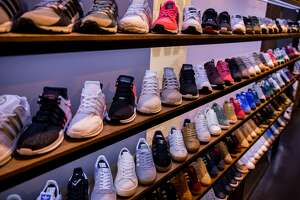 """BERLIN, GERMANY - MARCH 31: Shoes are seen at """"Overkill"""" sneakers store on March 31, 2017 in Berlin, Germany during sale of New KAWS x Air Jordan IV sneakers. Several dozen die-hard sneakers fans have taken five days out of their lives to put their names on a list and maintain their presence in order to buy the limited-production shoes. 50 pairs went on sale on March 31 at Overkill, one of only three stores in Germany to sell the shoes. At EUR 350 a pair the shoes carry a hefty price tag, but many of the buyers will resell them, for prices they predict could reach EUR 4,000. Sportswear companies like Adidas and Nike have hired famous designers for limited-production sneakers as the appetite for the shoes by sneakers fanatics has grown into a niche market over the last few years. (Photo by Maja Hitij/Getty Images)"""