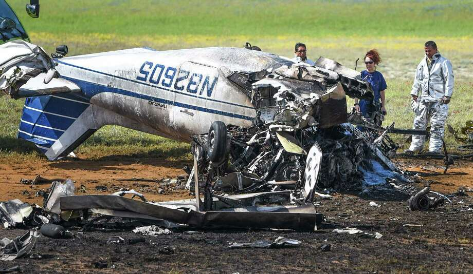 Laredo firefighters and Webb County Medical Examiner Corinne Stern look through the wreckage of a small plane that crashed at the Laredo International Airport on Thursday, Mar. 8, 2018. The Laredo Police Department confirmed there were two fatalities as a result of the crash. Photo: Danny Zaragoza, Laredo Morning Times