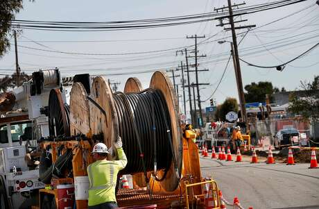 Huge spools of power lines are prepared to be installed as P.G. & E. runs power lines underground along Old Country Rd. near Harbor Way, with plans on removing the overhead power poles in six weeks, in Belmont, Calif., on Tues. Mar. 6, 2018.