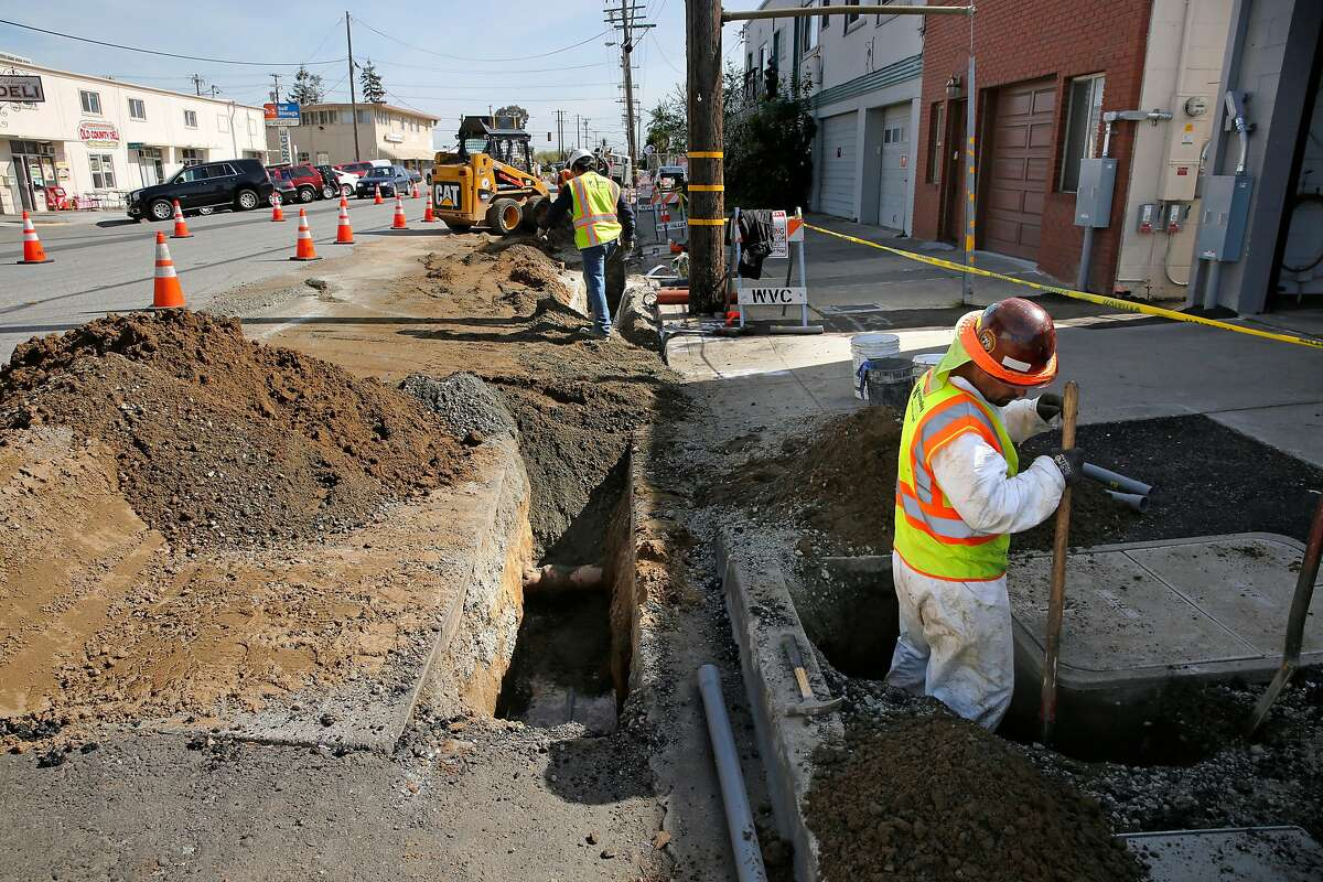 Workers dig ditches that will carry the P.G. & E. power lines underground along Old Country Rd. near Harbor Way, with plans on removing the overhead power poles in six weeks, in Belmont, Calif., on Tues. Mar. 6, 2018.