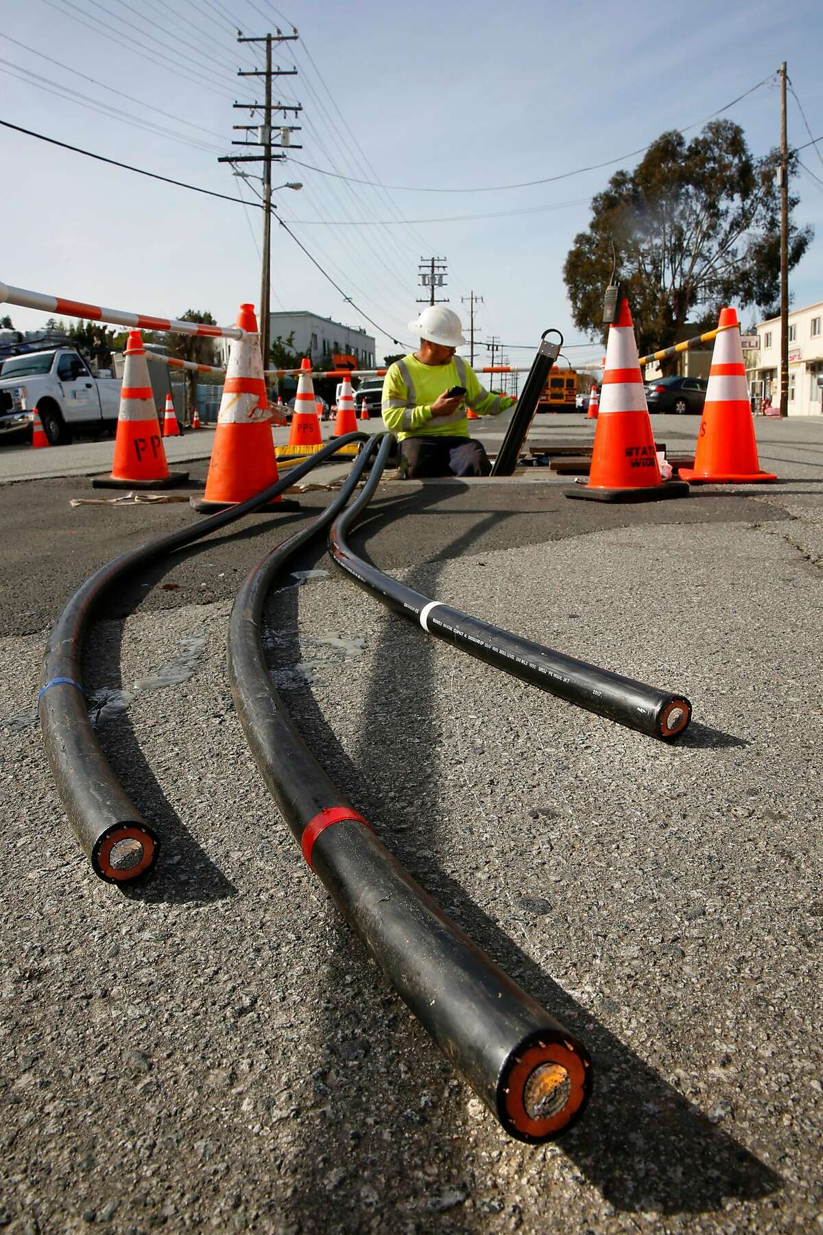 Zach Braun with Pinnacle Power helps to install P. G. and E. power lines underground along Old Country Rd. near Harbor Way, with plans on removing the overhead power poles in six weeks, in Belmont, Calif., on Tues. Mar. 6, 2018.