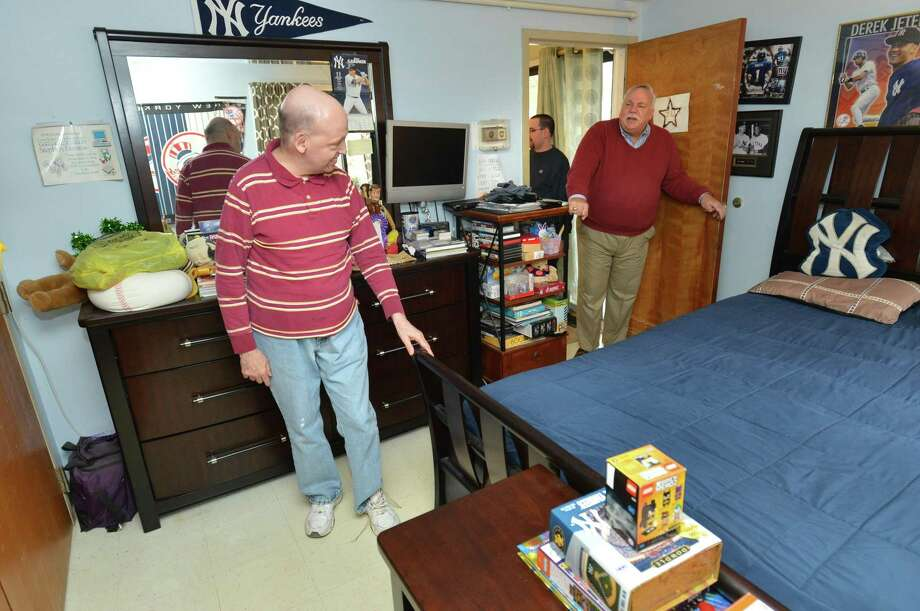 Resident Stephen Denittis shows some of the sports items in his room at Stoler House to STAR Director of Philanthropy Peter Saverine at Star Inc. on Monday in Norwalk. Photo: Alex Von Kleydorff / Hearst Connecticut Media / Norwalk Hour
